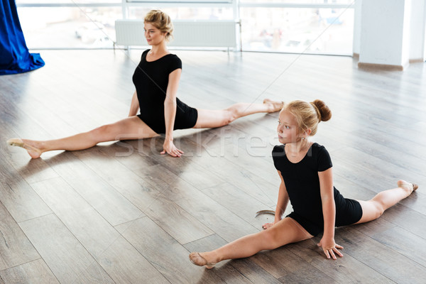 Little girl ballerina and teacher doing twine in ballet class Stock photo © deandrobot