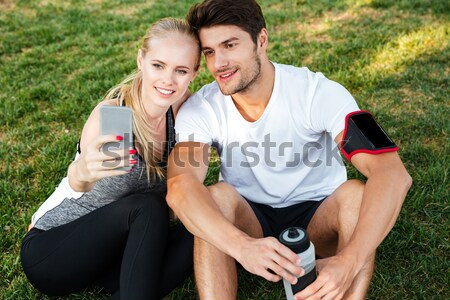 Smiling young woman and personal trainer with smartphone Stock photo © deandrobot
