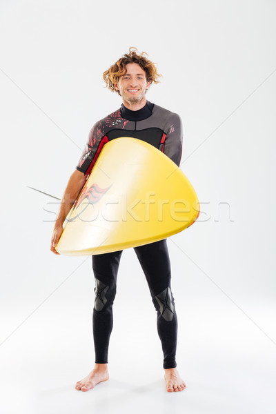 Full length portrait of a smiling surfer holding surf board Stock photo © deandrobot