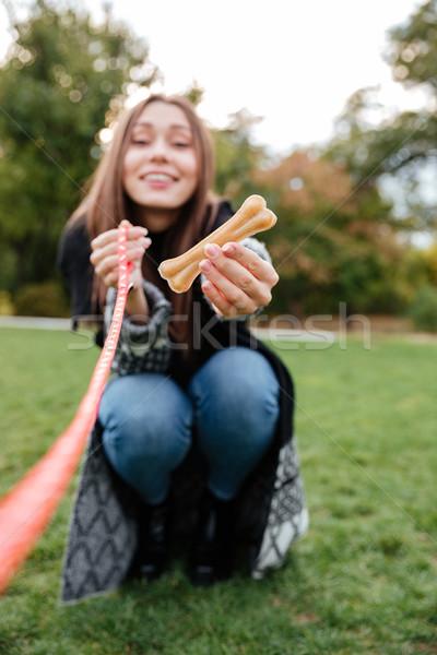 Sorridente mulher jovem osso cão encantador ao ar livre Foto stock © deandrobot