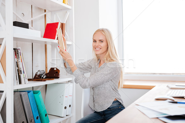 Young business woman taking book from a shelf in office Stock photo © deandrobot