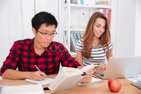 Cheerful students working with books and laptop in classroom Stock photo © deandrobot
