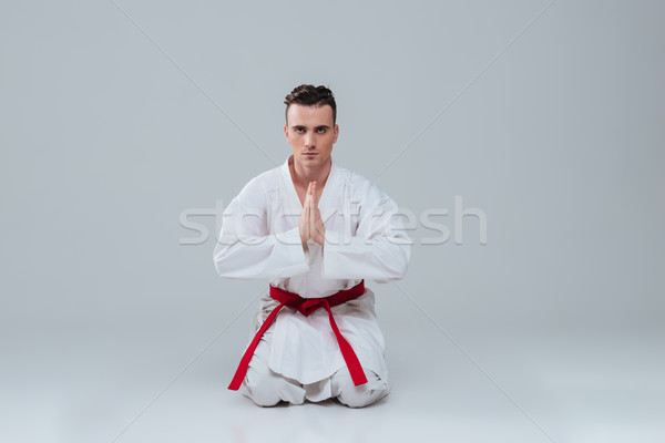 Handsome young sportsman sitting on floor in kimono Stock photo © deandrobot