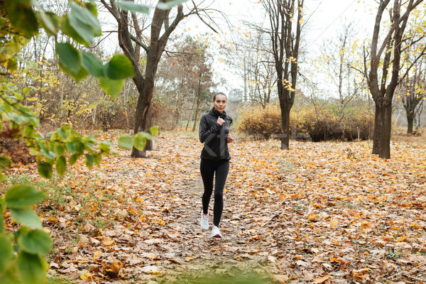 Young woman runner in warm clothes and earphones Stock photo © deandrobot