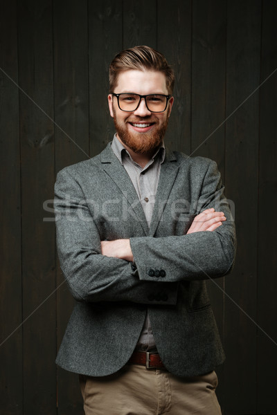 Smiling bearded young businessman standing with arms folded Stock photo © deandrobot