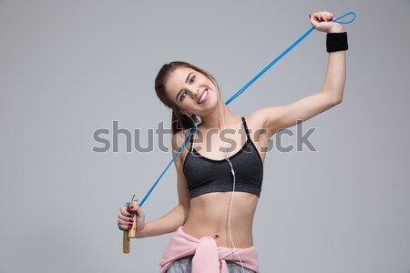 Young concentrated fitness woman doing exercises with small barbells Stock photo © deandrobot