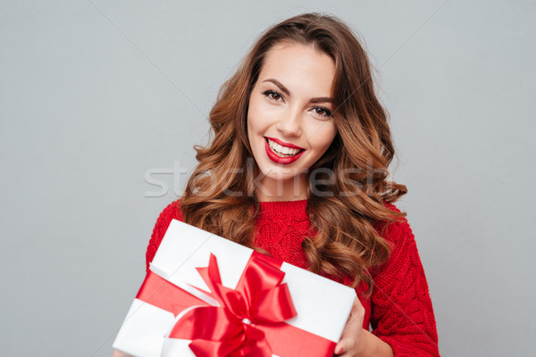 Smiling woman in red sweater with a box Stock photo © deandrobot