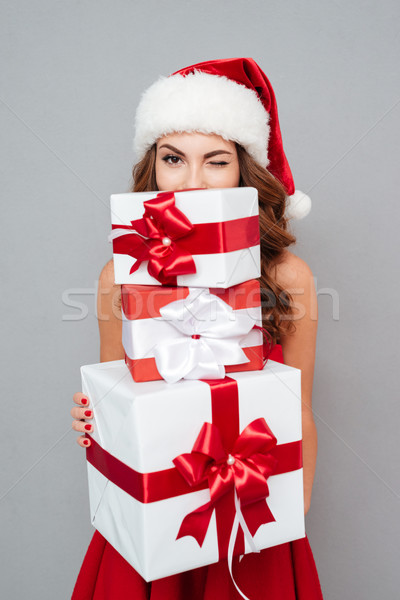 Girl hiding behind christmas gifts and winks Stock photo © deandrobot