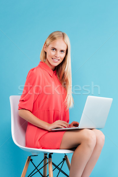 Woman in red dress with laptop sitting on the chair Stock photo © deandrobot