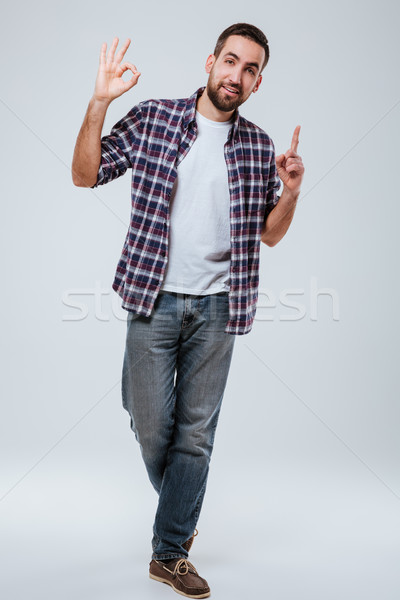 Full length portrait man showing ok sign and pointing up Stock photo © deandrobot