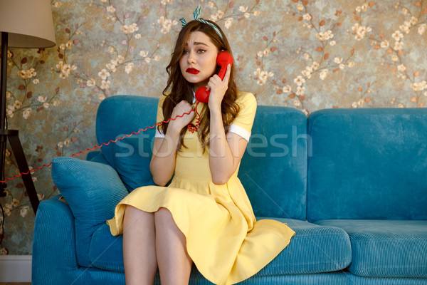 Sad young pin-up lady talking by phone. Stock photo © deandrobot