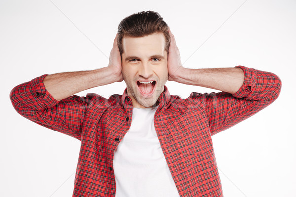 Screaming man covering his ears Stock photo © deandrobot