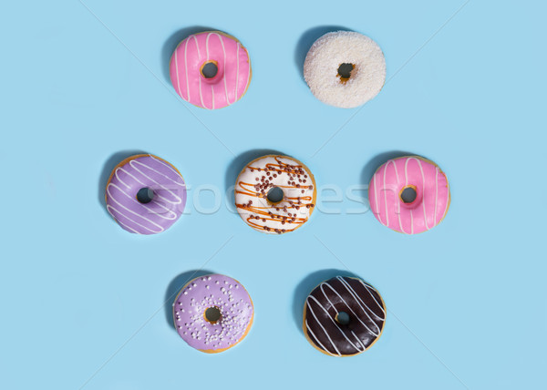 Sweeties donuts over blue table background. Stock photo © deandrobot