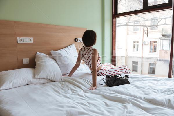 Сток-фото: красивая · женщина · сидят · кровать · глядя · окна · вид · сзади