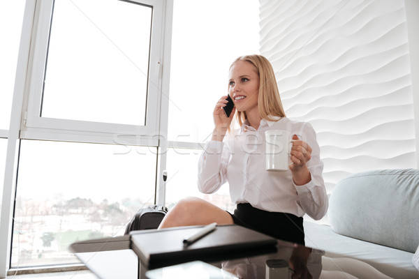 Business woman sitting in office while talking by phone Stock photo © deandrobot
