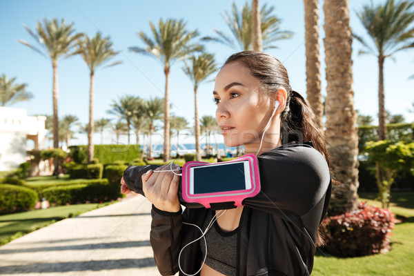 Fitness woman with blank screen smartphone in armband stretching arms Stock photo © deandrobot
