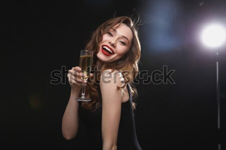 Cheerful beautiful young woman drinking champagne and winking Stock photo © deandrobot