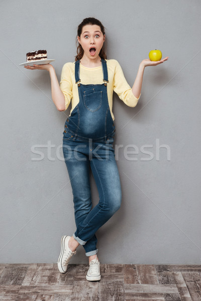 Shocked pregnant lady holding sweet cake and apple. Stock photo © deandrobot