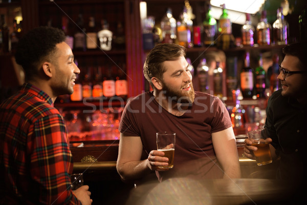 Smiling young men drinking beer Stock photo © deandrobot
