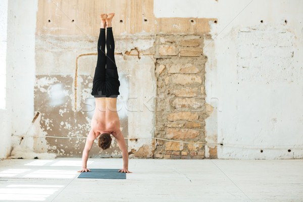 Full length back view of a man practising yoga poses Stock photo © deandrobot