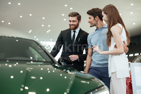 Handsome young car salesman telling a young couple Stock photo © deandrobot