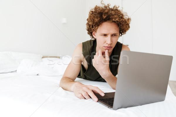 Foto stock: Concentrado · hombre · mentiras · cama · casa · usando · la · computadora · portátil
