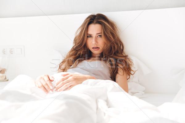 Jóvenes triste dama mentiras cama Foto stock © deandrobot