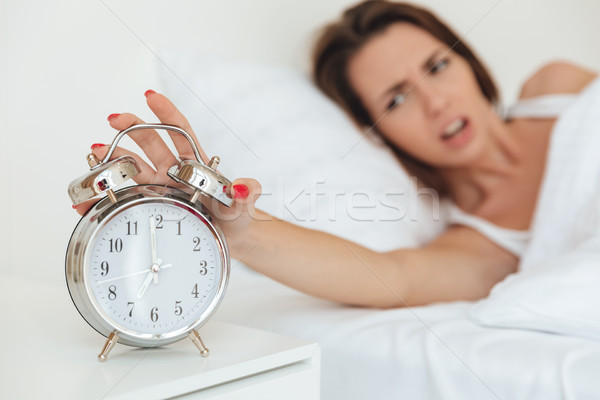 Close up of a woman turning off alarm clock Stock photo © deandrobot