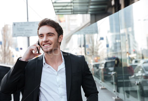 Happy young businessman walking near business center Stock photo © deandrobot