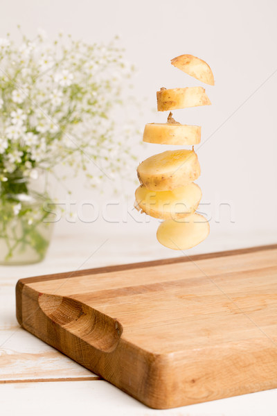 Sliced whole potatoe flying above a wooden chopping board Stock photo © deandrobot