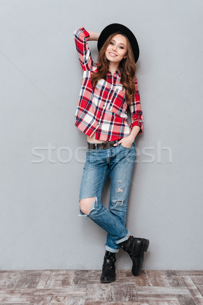 Smiling stylish woman in plaid shirt standing and posing Stock photo © deandrobot
