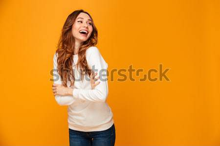 Woman in dress standing and winking with her arms crossed Stock photo © deandrobot