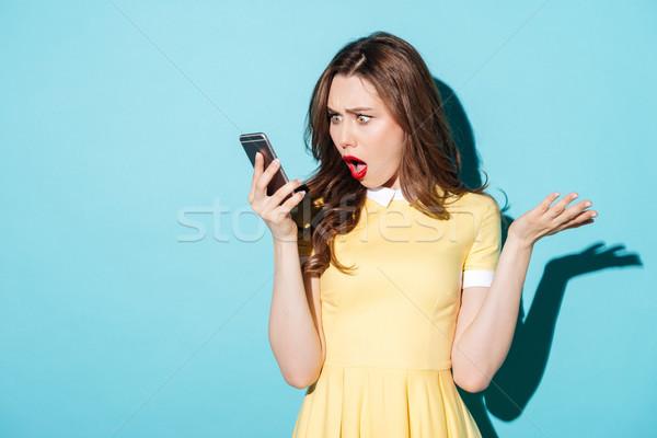 Sorprendido confundirse mujer vestido mirando teléfono móvil Foto stock © deandrobot