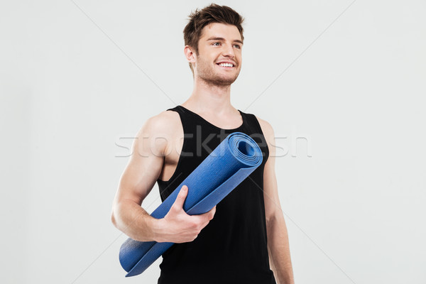 Smiling young sportsman holding fitness rug Stock photo © deandrobot