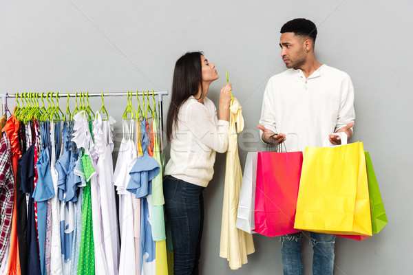 Lady begging clothes from confused man holding shopping bags. Stock photo © deandrobot