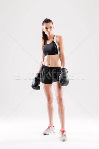 Portrait of a serious motivated woman in boxing gloves standing Stock photo © deandrobot
