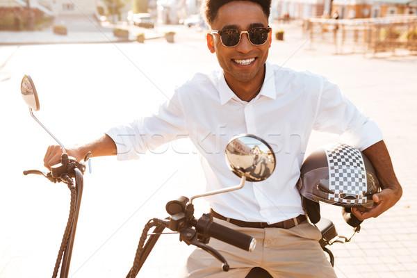 Smiling african man sitting on modern motorbike outdoors Stock photo © deandrobot