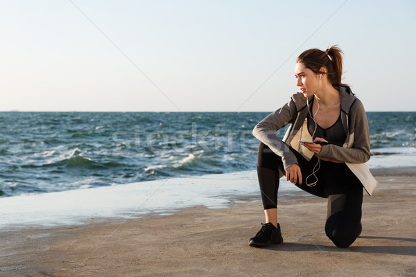 Photo of young healthy sport woman sitting on knee, holding smar Stock photo © deandrobot
