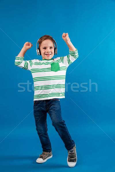 Full length image of carefree young boy listening music Stock photo © deandrobot