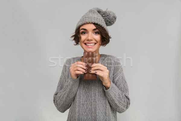 Cheerful woman dressed in sweater and warm hat holding chocolate. Stock photo © deandrobot