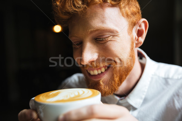 Close-up portrait of smiling curly readhead bearded man tasting  Stock photo © deandrobot