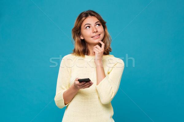 Pensive femme souriante chandail smartphone up Photo stock © deandrobot