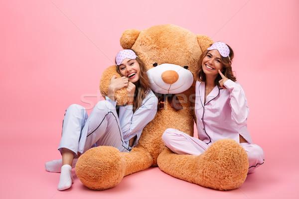 Kettő mosolyog csinos lányok pizsama ül Stock fotó © deandrobot