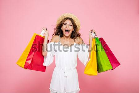 Portrait of a brown haired girl holding colorful shopping bags Stock photo © deandrobot