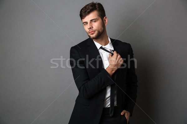 Handsome confident young business man in black suit straightenin Stock photo © deandrobot