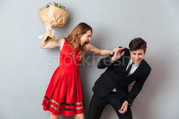 Portrait of a furious woman beating a man Stock photo © deandrobot