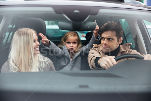 Emotional young man sitting in car with his funny wife Stock photo © deandrobot