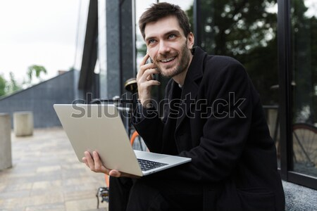 Cheerful business man in eyeglasses sitting by table in cafe Stock photo © deandrobot