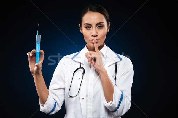 Calm serious lady holding syringe and making silence gesture isolated Stock photo © deandrobot