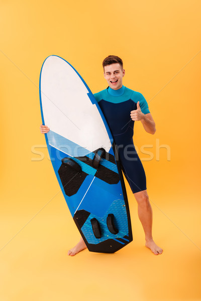 Full length portrait of happy hansome surfer showing thumb up  gesture while standing and holding su Stock photo © deandrobot